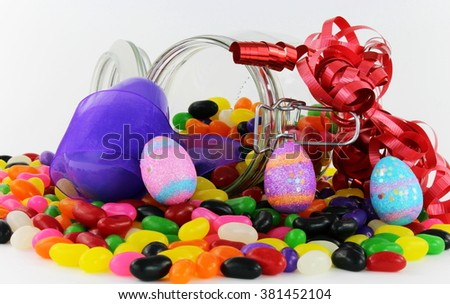 Jelly Beans in Glass Jar with Purple Easter Egg, Purple and Red Ribbon and smaller Easter eggs - stock photo