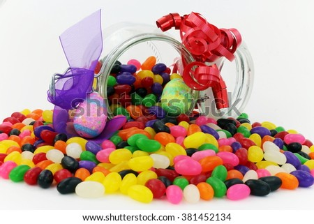 Jelly Beans in Glass Jar with small Easter Eggs and Purple and Red Ribbon - stock photo