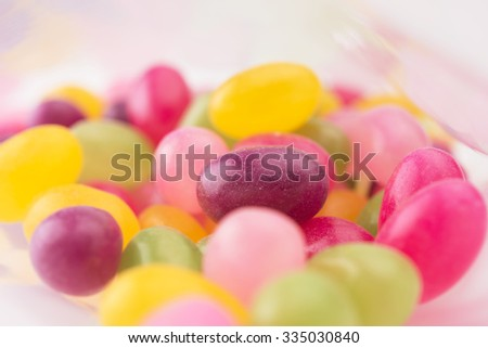 Jelly beans or sugar coated gummy candy inside a plastic bag. Shallow depth of field. - stock photo