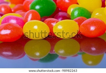 Jelly beans reflected in glossy black table