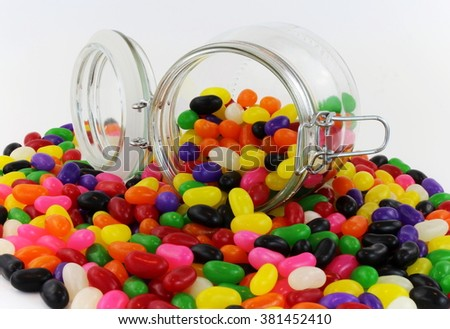 Jelly Beans spilt from Glass Jar with Lid - stock photo