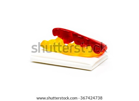 Jelly bears making love on a folded paper tissue - with shadow on white background - stock photo