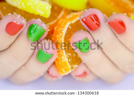 Jelly candies in hands with manicure - stock photo