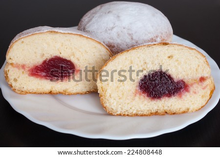 Jelly filled doughnuts on white plate on black wooden background - stock photo