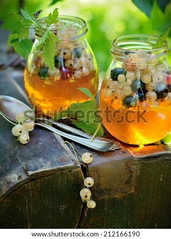 Jelly with fresh berries on wooden table outdoor - stock photo
