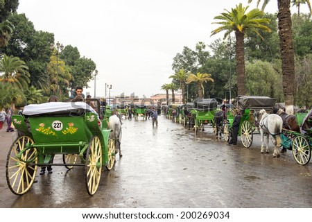 JEMMA DAR FNA, THE MAIN BAZAAR, MARRAKECH, MOROCCO, MAY 11, 2014. Horse wagons at the street which leads into Jemma Dar Fna,  Marrakech, Morocco, on May 11th, 2014.  - stock photo