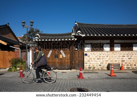 JEONJU, SOUTH KOREA - 03 NOVEMBER 2014: An unidentified cyclist cycles past old traditional Korean houses in this vintage town. The Korean Hanok Village in Jeonju is a major tourist attraction. - stock photo