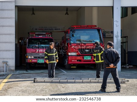 JEONJU, SOUTH KOREA - 3 NOVEMBER 2014: Firefighters prepare to start morning drills and practices in a fire department station in the Jeonju traditional Korean Hanok village. - stock photo