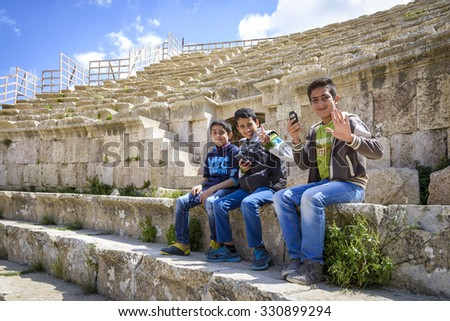 Jerash, Jordan - April 04, 2015: View of unidentified smiling boys sitting in the Roman Theater of Jerash. Jerash (Gerasa of Antiquity), is the second-most popular tourist attraction in Jordan. - stock photo