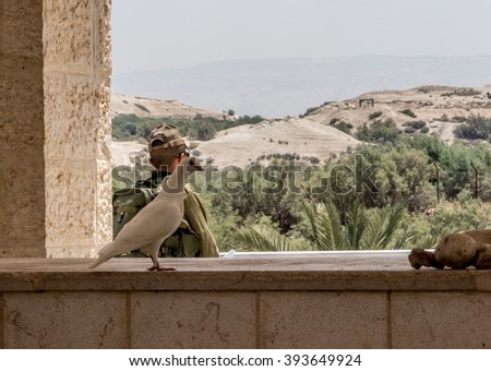 JERICHO, ISRAEL - JULY 14, 2014: Israel's borders with Jordan at the site of Jesus' baptism site in Jordan Qasr el Yahud  a soldier patrolling the border, peace dove and the dove of the Holy Spirit - stock photo