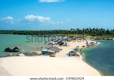 Jericoacoara, Ceara state, Brazil - July 2016: Lagoon Tatajuba from above; trucks, buggy and other 4x4 transport with tourists traveling through the desert