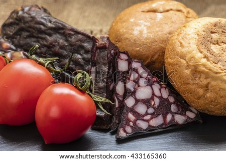 jerked sausage with vegetables on a dark background