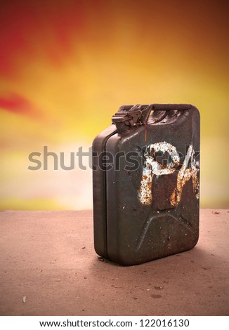 jerry can on sand at sunset - stock photo