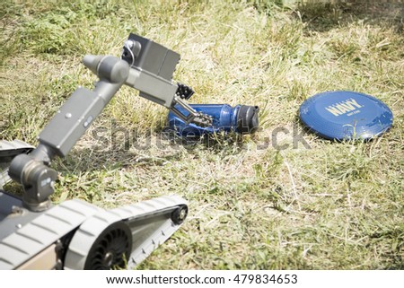 JERSEY CITY NJ MAY 29 2016: A small unmanned ground vehicle the US Navy uses to locate and dispose of explosive devices picks up a travel mug at a demonstration in Liberty State Park, Fleet Week 2016.