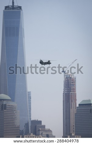 JERSEY CITY, NJ - MAY 26 2015: A US Marine Corps helicopter flies past the Freedom Tower and WFC on the Upper New York Bay before the USS San Antonio departs Pier 92 at the end of Fleet Week NY 2015. - stock photo