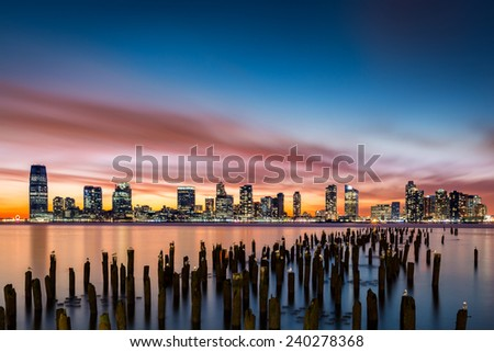Jersey City skyline at sunset as viewed from Tribeca, New York, across the Hudson River - stock photo