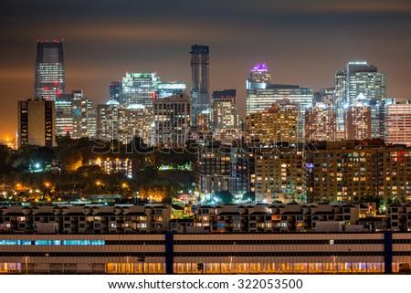 Jersey City skyline rises behind Hoboken and Weehawken cities. - stock photo