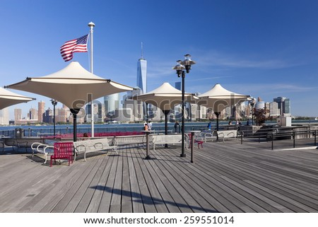 JERSEY CITY, USA-OCTOBER 3, 2014: Hudson River waterfront park at Exchange Place is named in honor J.Owen Grundy. Amazing view of the Freedom Tower and of lower Manhattan - stock photo