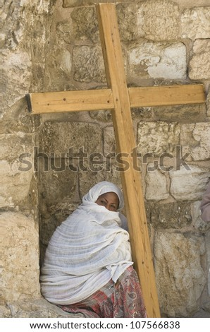 JERUSALEM - APRIL 13 : Ethiopian Christian pilgrim sit with across at the church of the Holy sepulchre in Jerusalem israel during Good Friday on April 13 2012 - stock photo