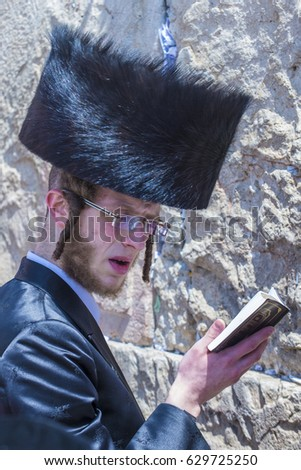 JERUSALEM - APRIL 13 : Orthodox jewish man prays in The western wall during Passover on April 13 2017 , The Western wall is important Jewish religious site located in the Old City of Jerusalem