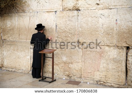 JERUSALEM - DECEMBER 30, 2013 - Orthodox jewish man prays at the Western Wall. An Important Jewish religious site located in the Old City of Jerusalem , Israel, 30.12.2013 - stock photo