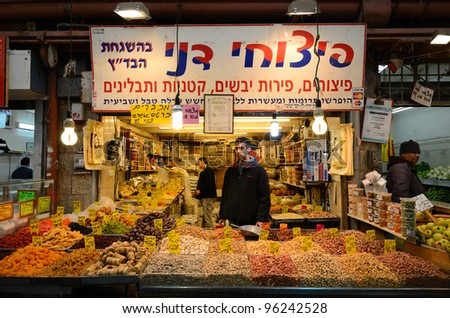 JERUSALEM - FEBRUARY 16: An Israeli vendor sells dried fruits and nuts in a souq February 16, 2012 in Jerusalem, IL. Souqs are markets common to the middle east which sell food and other essentials. - stock photo