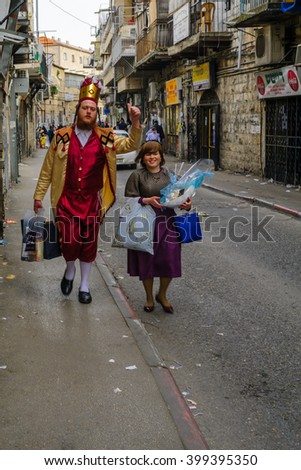 JERUSALEM, ISR - FEB 25, 2016: Street scene of people carrying mishloach manot (portions to the poor), a Jewish Holyday Purim tradition, the ultra-orthodox neighborhood Mea Shearim, Jerusalem, Israel - stock photo
