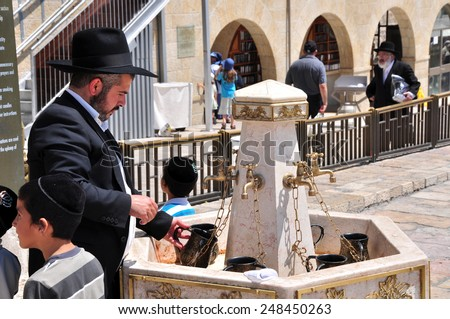 JERUSALEM, ISRAEL - CIRCA AUGUST 2014: Man performs ablutions before prayer at the Western Wall circa Augusy 2014 in Jerusalem, Israel.