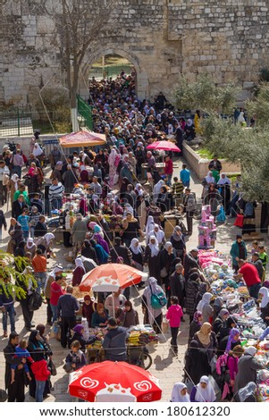 Jerusalem , Israel - February 22 , 2014 : Bazaar at the exit of Al-Aqsa Mosque in the Old City of Jerusalem .Men and women buy different products at the outlet of the Al-Aqsa Mosque after prayers.