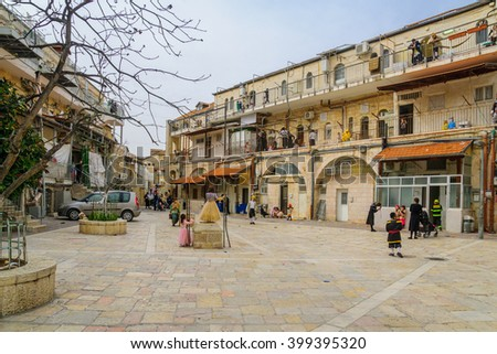 JERUSALEM, ISRAEL - FEBRUARY 25, 2016: Street scene of the Jewish Holyday Purim, with locals, some wearing costumes, in Batei Ungarin, the ultra-orthodox neighborhood Mea Shearim, Jerusalem, Israel - stock photo