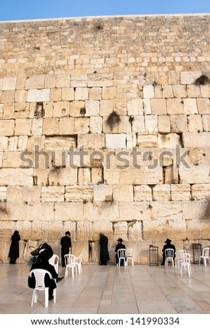 JERUSALEM, ISRAEL - JANUARY 26: Jewish worshipers pray at the Wailing Wall. The most holy site for Jews. January 26, 2011 in Jerusalem, Israel. - stock photo