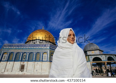 Jerusalem, Israel - January 10, 2014 : Muslim tourist near The Dome of Rock .  The Dome was constructed by the order of Caliph Abd al-Malik and considered sacred to Muslims. - stock photo