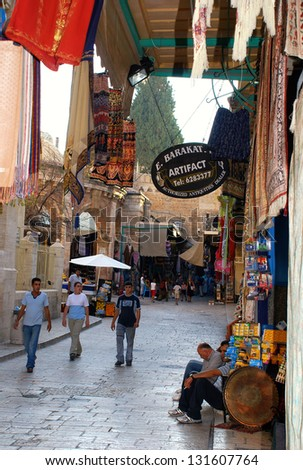 JERUSALEM, ISRAEL - JULY 23: East market on narrow street in Jerusalem Old City  July 23, 2007. Old City has many small shops where you can buy fabrics, artifacts and souvenirs. - stock photo
