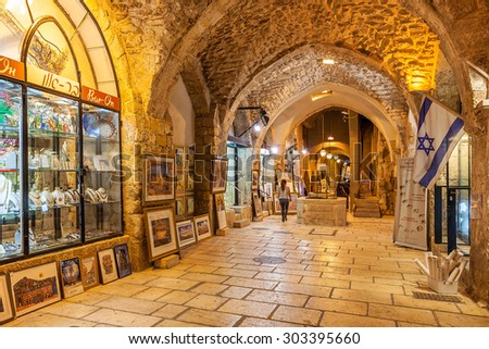 JERUSALEM, ISRAEL - JULY 16, 2015: Gift shops  gallery in ancient stone vault passage in Old City of Jerusalem - one of the oldest cities in the world and holy in Judaism, Islam and Christianity. - stock photo