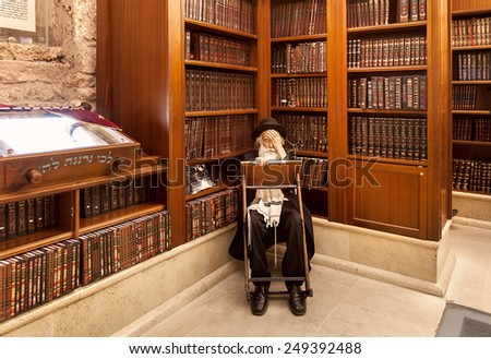 JERUSALEM, ISRAEL - JULY 10, 2014: Old rabbi learns Torah among wooden bookshelves with holy books in Cave Synagogue - old sacred place for Judaism which is part of famous Western Wall in Jerusalem. - stock photo