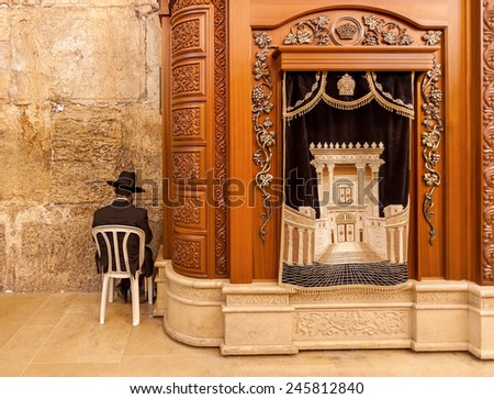 JERUSALEM, ISRAEL - JULY 10, 2014: Prayer sits near Carving wooden cabinet with Torah scrolls in Cave Synagogue - a part of famous Western Wall (aka Wailing Wall), sacred place in Judaism. - stock photo