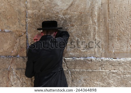 Jerusalem, Israel - March 24 2015 : Orthodox Jewish man pray at the western wall. The western wall is an exposed section of ancient wall situated on the western flank of the Temple Mount. - stock photo