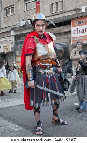 JERUSALEM, ISRAEL - MARCH 15, 2006: Purim carnival. A young man dressed in a suit of a Roman soldier with a sword in his hand. Purim is celebrated annually according to the Hebrew calendar.