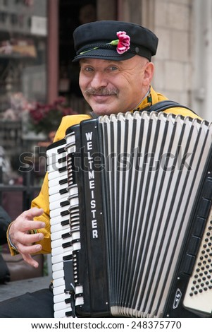 JERUSALEM, ISRAEL - MARCH 15, 2006: Purim carnival, street musician plays the accordion. Purim is celebrated annually according to the Hebrew calendar.  - stock photo
