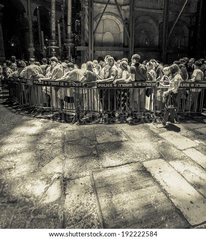 JERUSALEM, ISRAEL - MAY 26, 2013: The Church of the Holy Sepulchre is considered the greatest Christian shrine in the world. Pilgrims at the Church of the Holy Sepulchre in Jerusalem (stylized retro) - stock photo