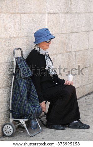 JERUSALEM, ISRAEL - NOVEMBER 21, 2010: An unidentified Caucasian woman is begging in the street next to the Western wall - stock photo