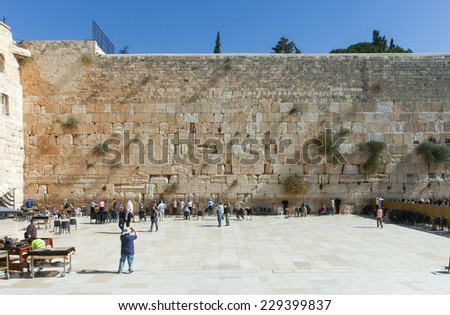 Jerusalem, Israel - November 9, 2014 : Local People and tourists pray at the western wall. The western wall is an exposed section of ancient wall situated on the western flank of the Temple Mount.