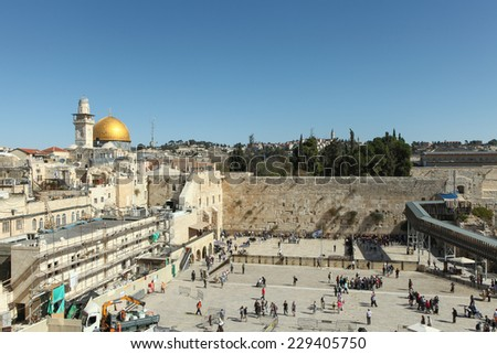 Jerusalem, Israel - November 9, 2014 : Panoramic view of the wailing wall with the Dome of the rock in the background with Local People and tourists pray at the western wall.  - stock photo