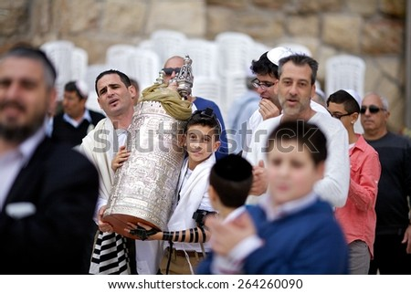 JERUSALEM, ISRAEL - November 18, 2013: 13 years old boy are carrying a torah scroll during a Bar Mitzvah ritual at the Wailing wall in Jerusalem. - stock photo
