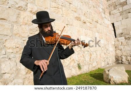 JERUSALEM, ISRAEL - OCT 07, 2014: A jewish fiddler is playing violin on the street near Jaffa gate in Jerusalem - stock photo