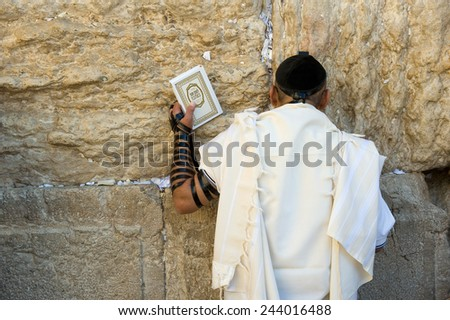 JERUSALEM, ISRAEL - OCT 06, 2014: A jewish man with the torah in his hand is praying against the western wall in the old city of Jerusalem - stock photo