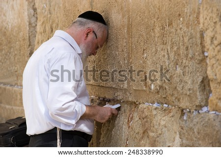 JERUSALEM, ISRAEL - OCT 07, 2014: A jewish man with the torah in his hands is praying in front of the western wall in the old city of Jerusalem - stock photo