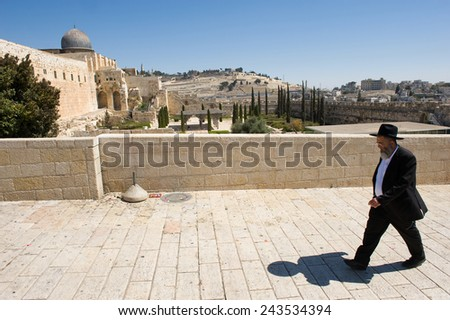 JERUSALEM, ISRAEL - OCT 06, 2014: An orthodox jewish man is walking on the street just southwest of the temple mount. On the left the Al-Aqsa mosque. - stock photo