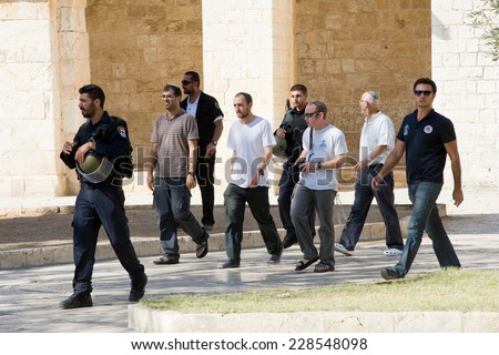 JERUSALEM, ISRAEL - OCT 08: Jews protected by security officers are walking on the temple-square and want to pray, this is the reason of the violence with muslims , October 08, 2014 in Israel - stock photo