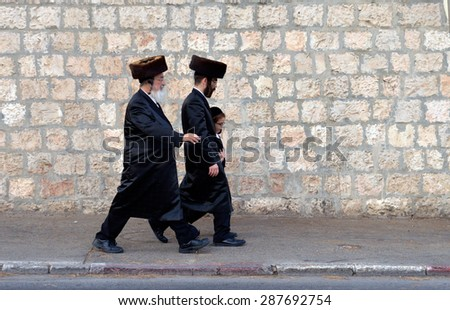 JERUSALEM, ISRAEL - OCT 09, 2014: Two Jewish men and a child walking on the street a few days before sukkot or the 'feast of tabernacles' - stock photo